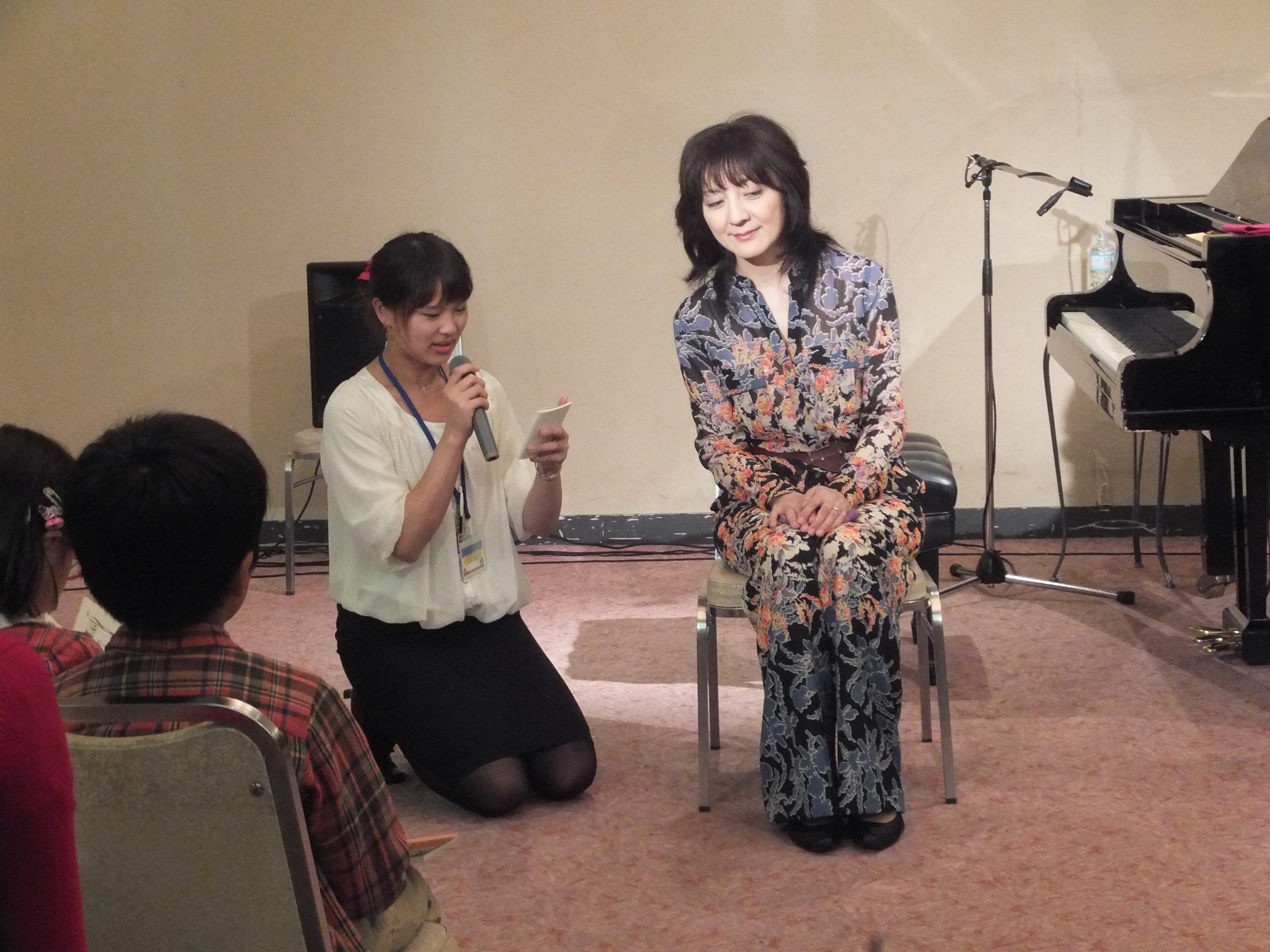 交流会で質問を読み上げる、主催者の益子有里さん。